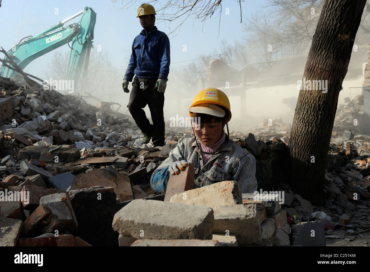 Chinese woman collecting bricks from ruins of demolished houses in central Beijing, China.20-Mar-2011 - Stock Image