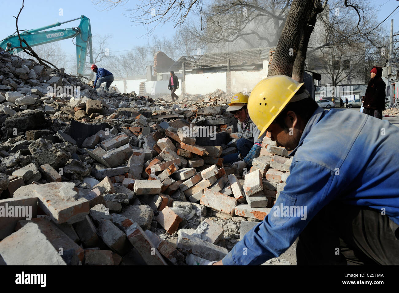 People collecting bricks from ruins of demolished houses in central Beijing, China.20-Mar-2011 - Stock Image