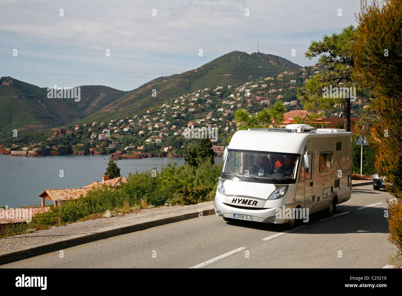 Camper van driving along the Esterel coast road, Var, Provence, France. - Stock Image