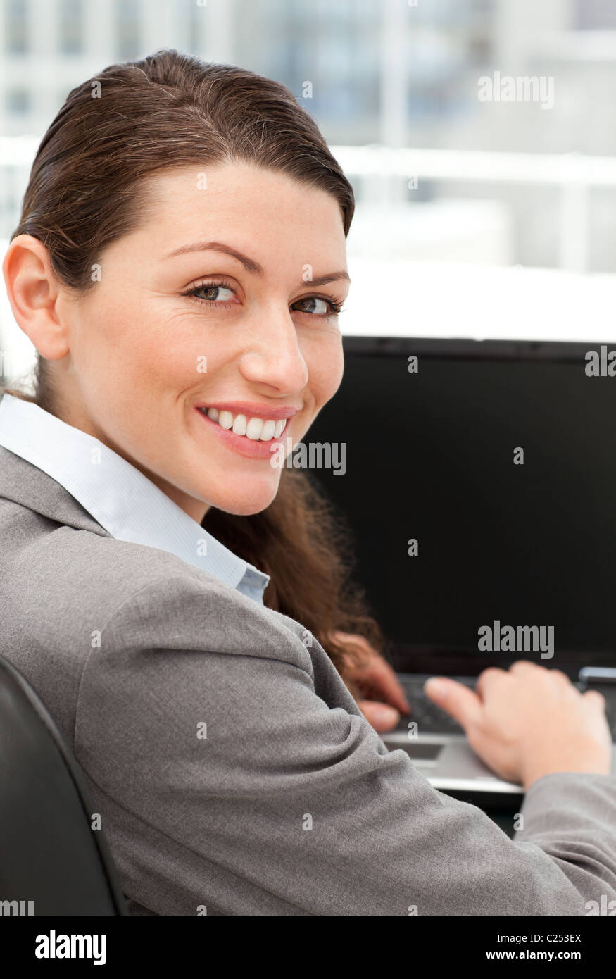 Rear view of a happy businesswoman working on her laptop - Stock Image