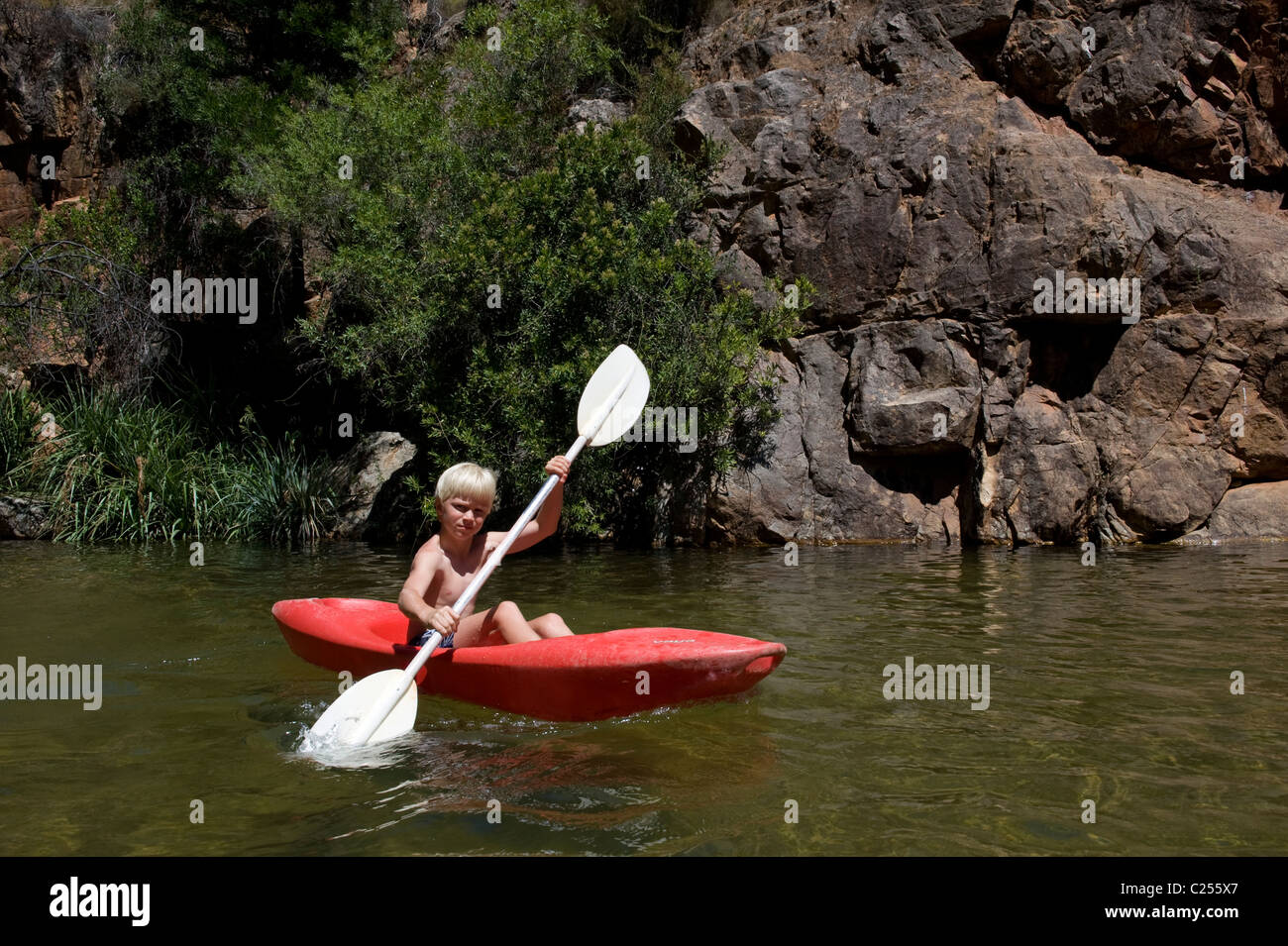 Boy paddling in a canoe on the Rondegat River, Cedarberg, Western Cape, South Africa - Stock Image