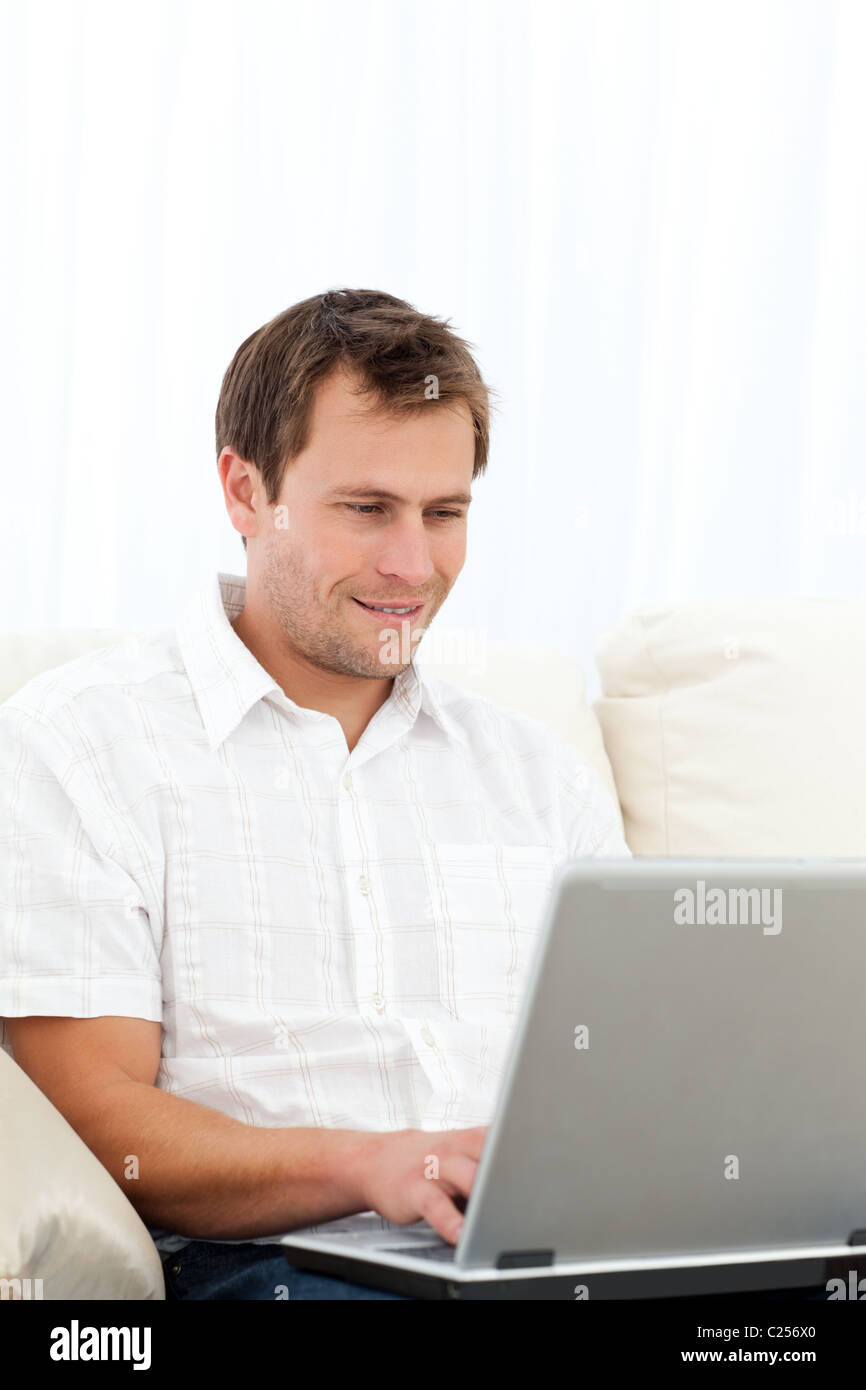 Happy man working on his laptop on the sofa - Stock Image