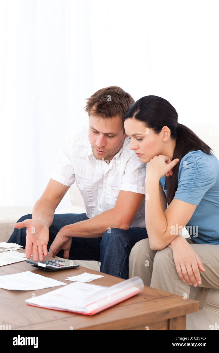 Desperate couple doing their account sitting on the sofa - Stock Image
