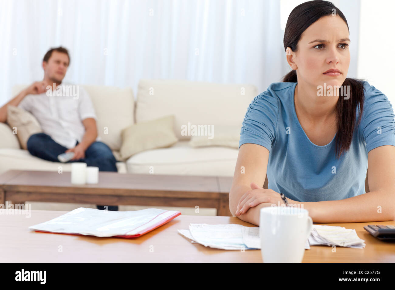 Angry woman doing her account while her boyfriend relaxing - Stock Image