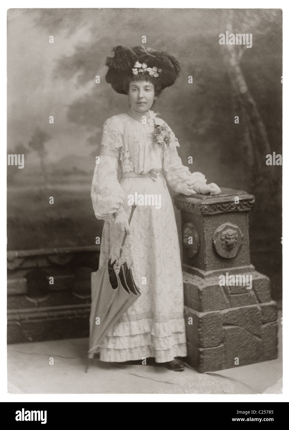 06b6f61a24d5a Studio portrait of fashionable, pretty young lady wearing a summer outfit,  feather hat, holding a parasol, in the Edwardian period, early 1900's  period ...