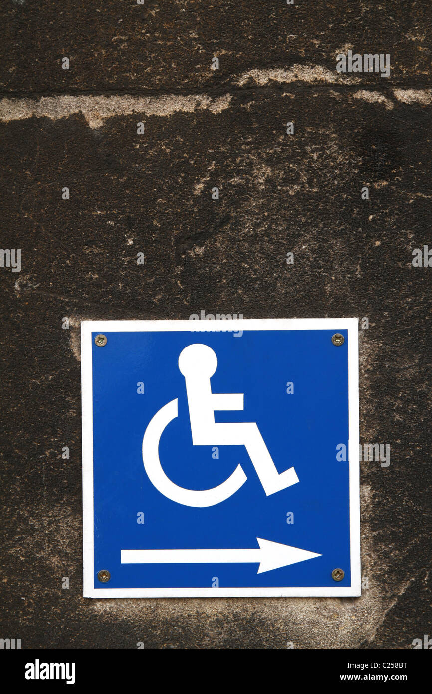 Disability access sign badge on a stone wall - Stock Image