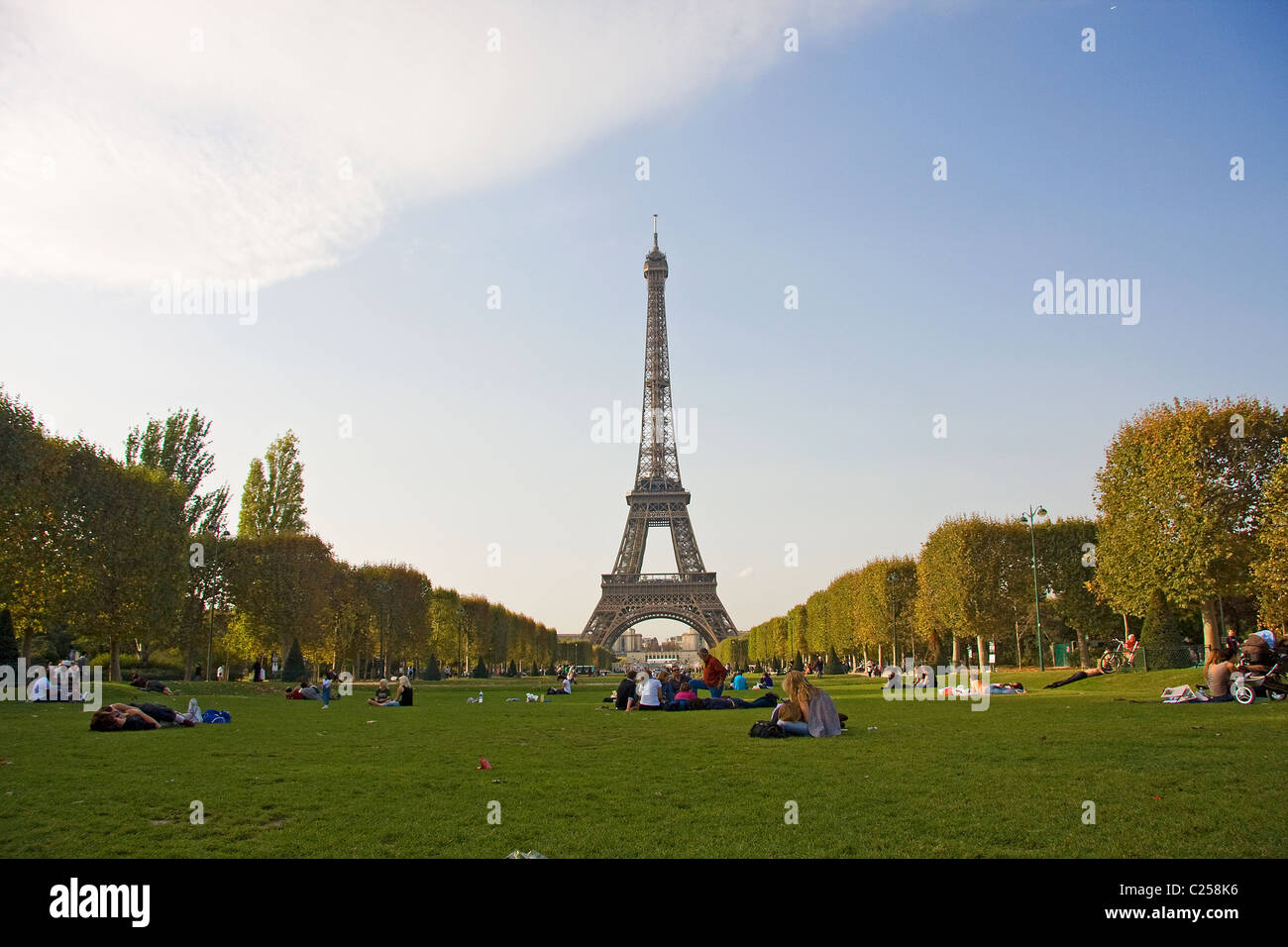 Parisians relax in the Parc du Champ de Mars, with the Eiffel Tower beyond - Stock Image