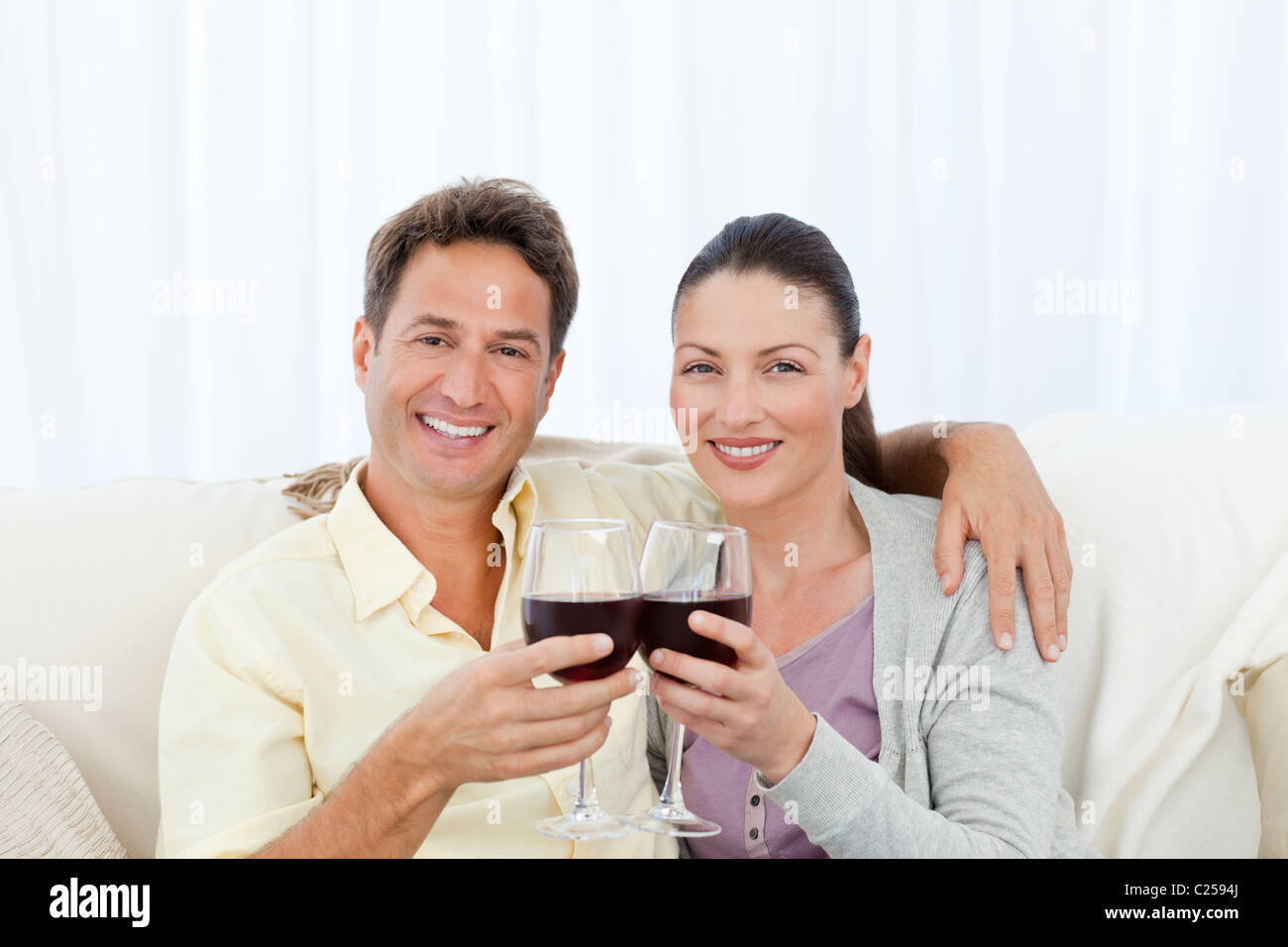Portrait of a couple clinking glasses of red wine on the sofa - Stock Image