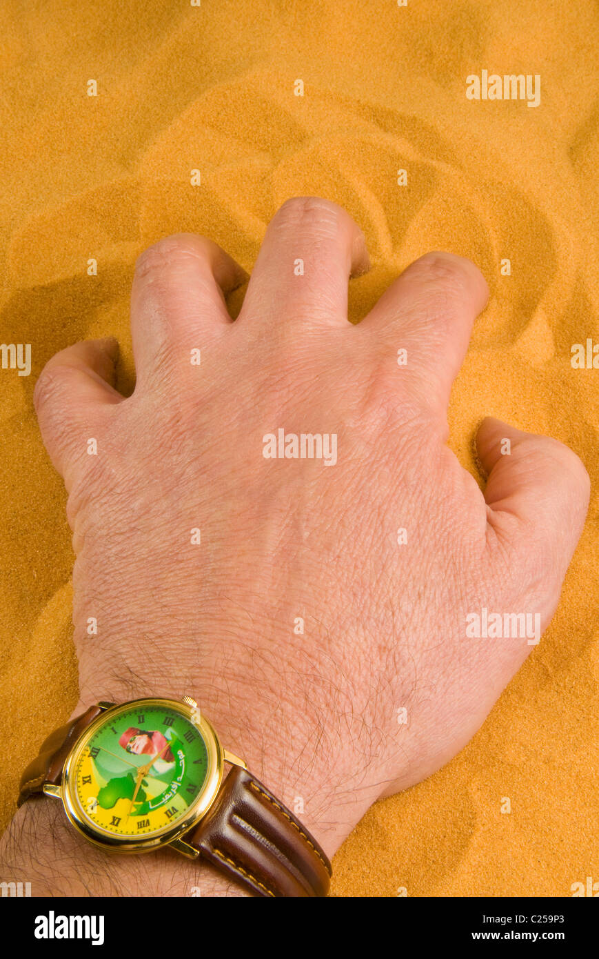 Hand and watch with the face of Muammar Muhammad al-Gaddafi leader of Libya on the Sahara sand - Stock Image