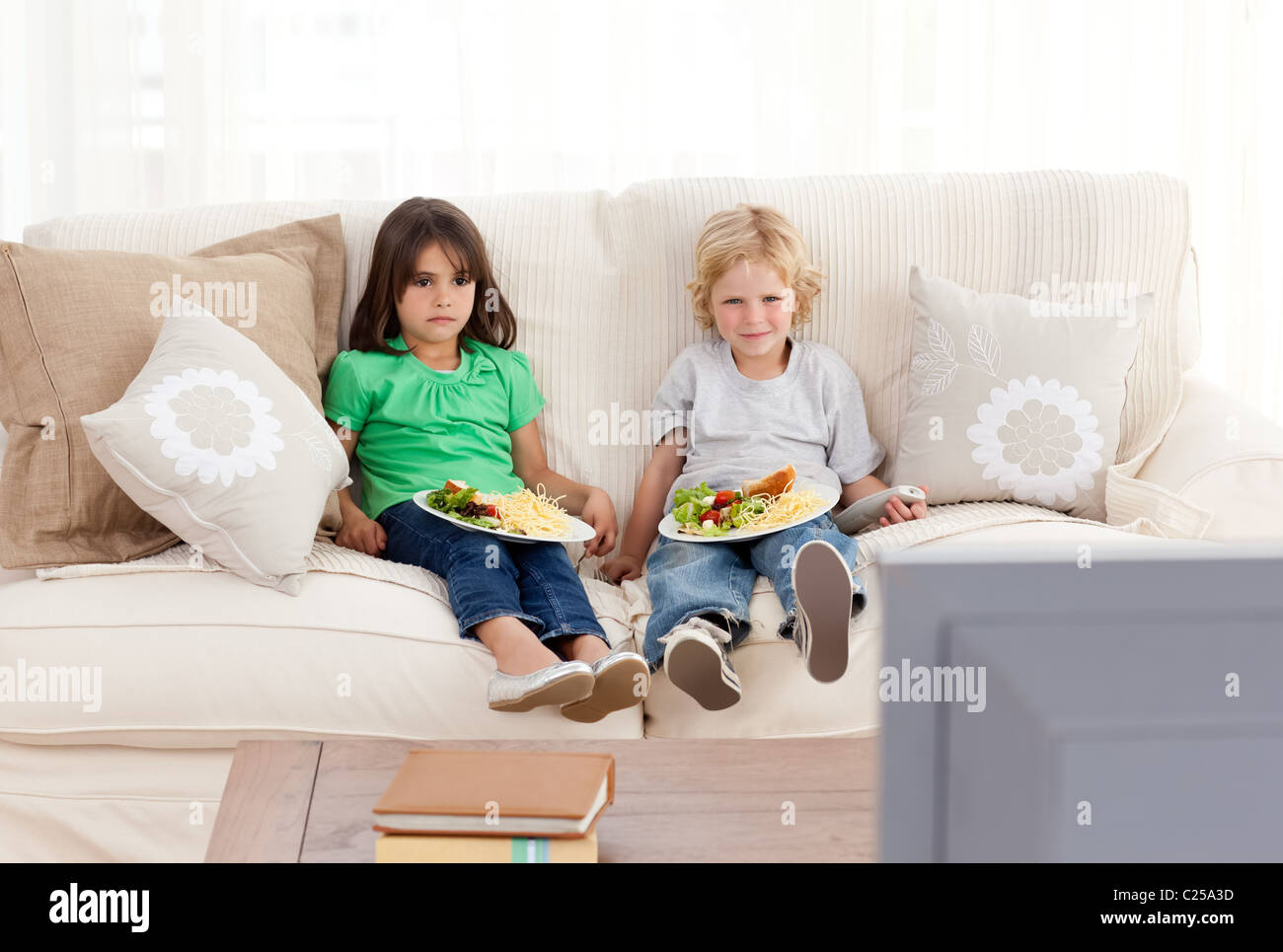 Cute brother and sister having dinner on the sofa - Stock Image