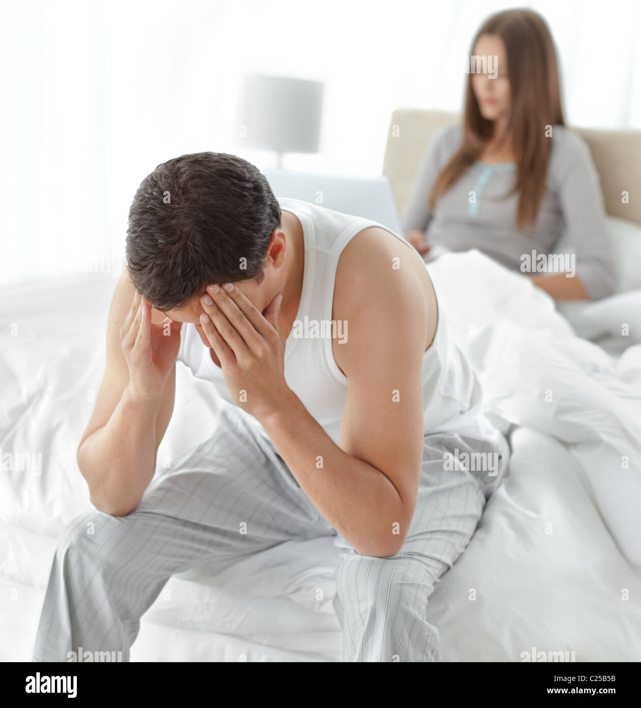 Stressed man sitting on his bed while his girlfriend working on the laptop - Stock Image