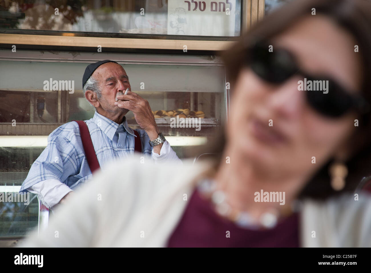Elderly Jewish man smoking in background with out of focus shalow depth of field woman in foreground - Stock Image