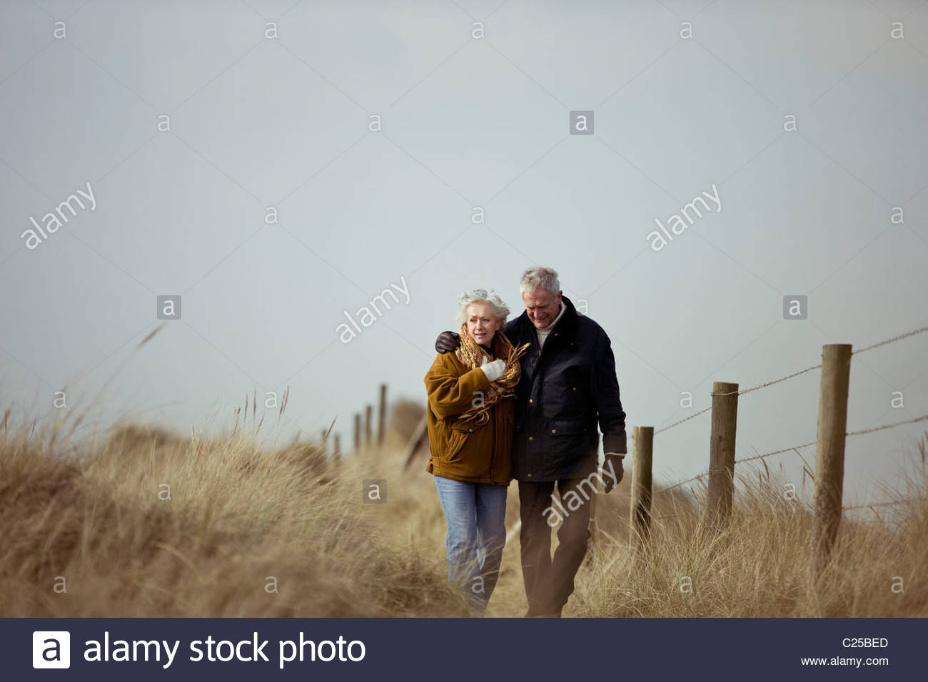A senior couple walking along a path together - Stock Image