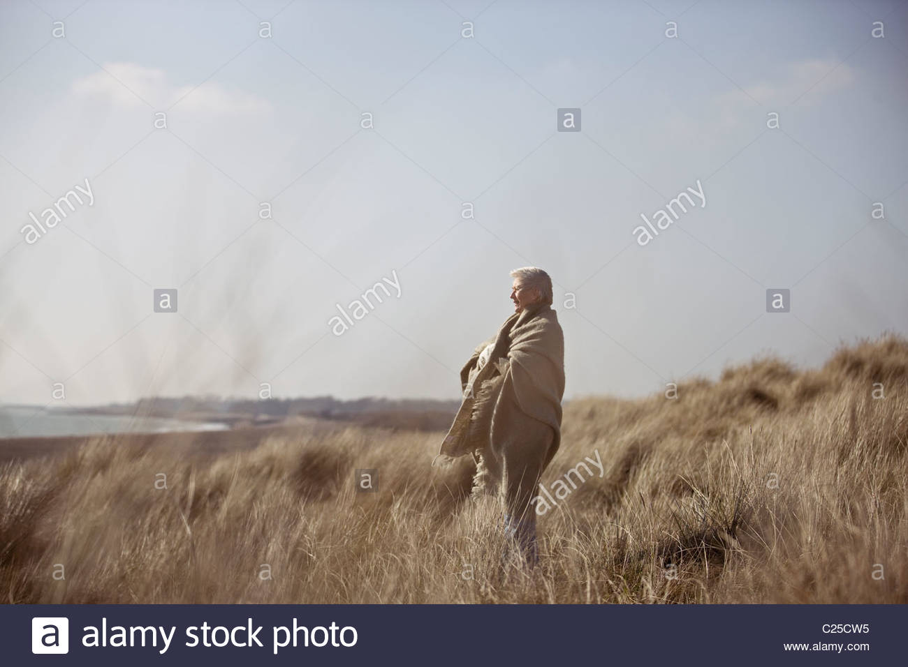 A senior woman standing amongst the sand dunes, wrapped in a blanket - Stock Image
