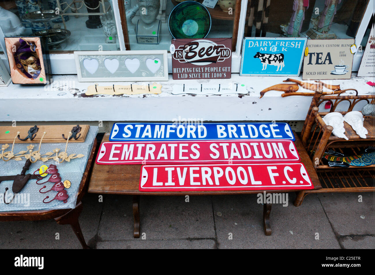 Reproduction football ground nameplates for sale as souvenirs together with old advertising signs in a junk shop - Stock Image