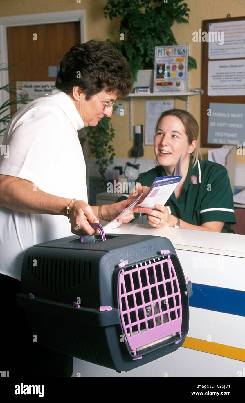 veterinary nurse handing leaflet to lady with cat in transporter - Stock Image