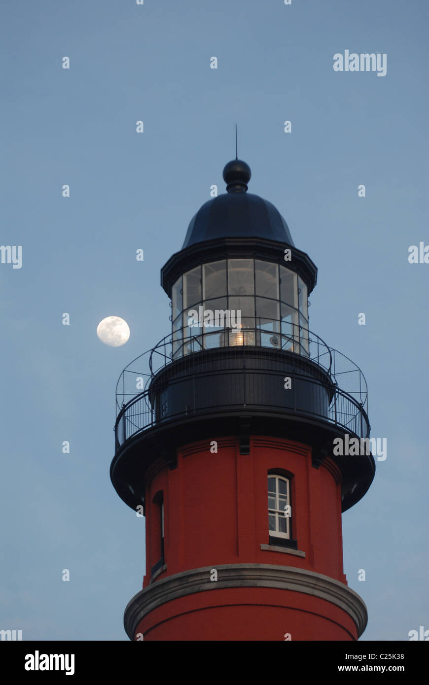 A moon rises behind a lighthouse at Ponce Inlet, Florida - Stock Image
