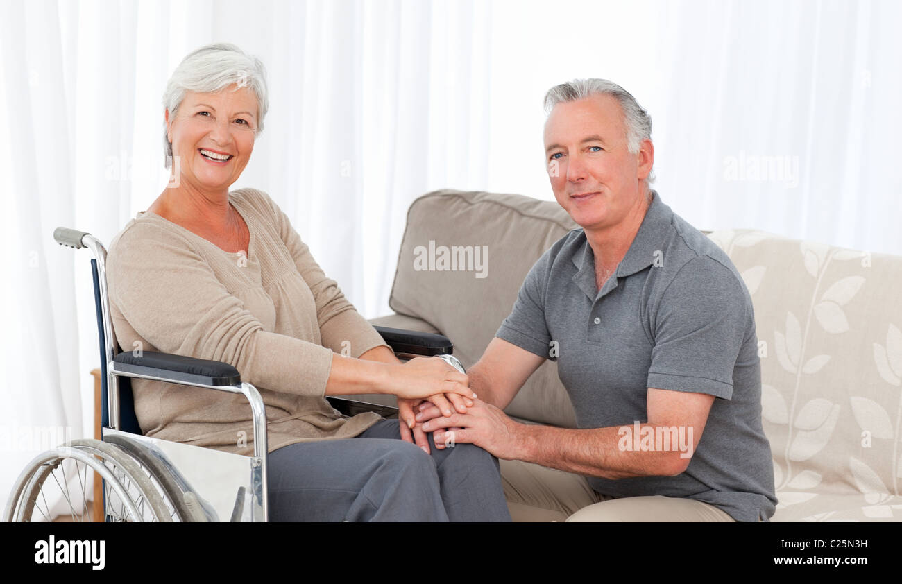 Man with his wife in a wheelchair - Stock Image