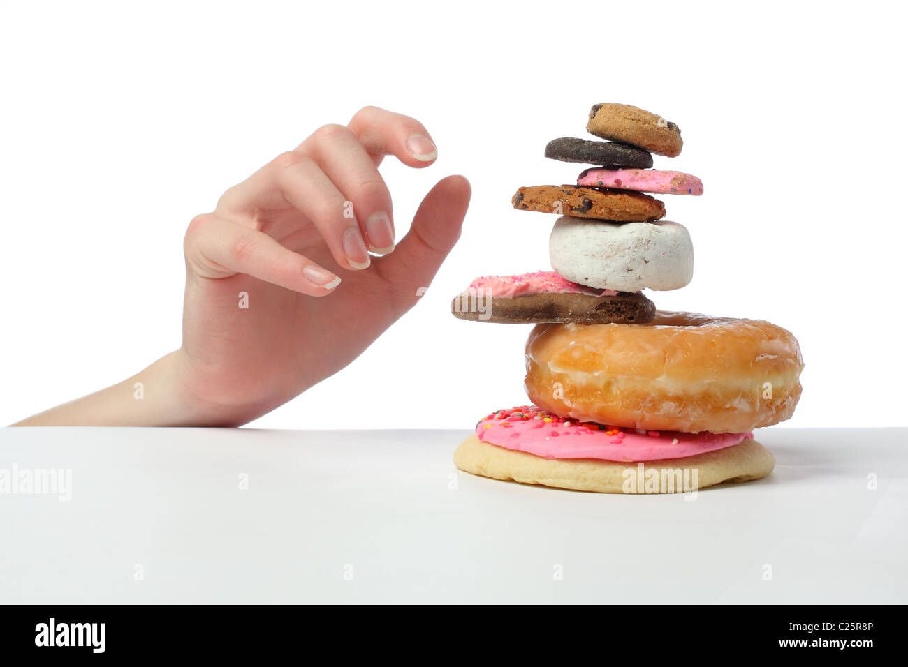 child hand reaching for cookie and pastry stack - Stock Image
