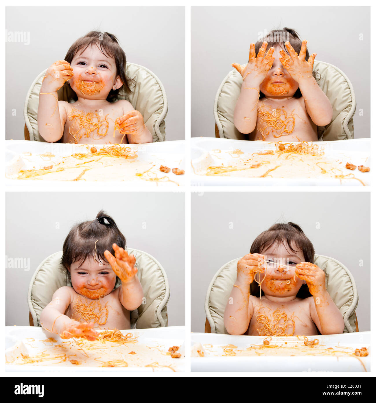 Happy baby having fun eating messy showing hands covered in Spaghetti Angel Hair Pasta red marinara tomato sauce. - Stock Image