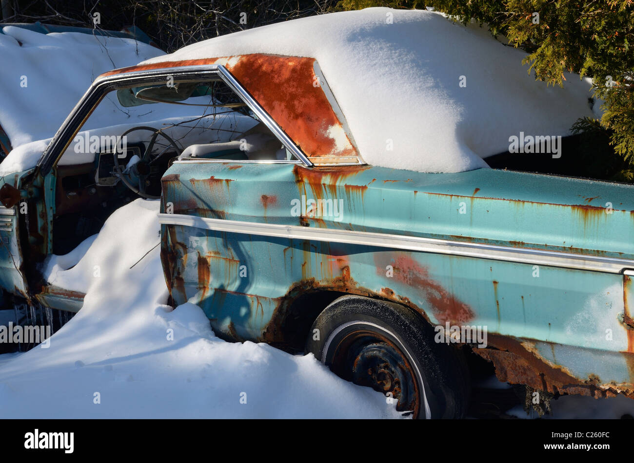 Fresh snow covering a rusting abandoned car on a frosty winter morning - Stock Image