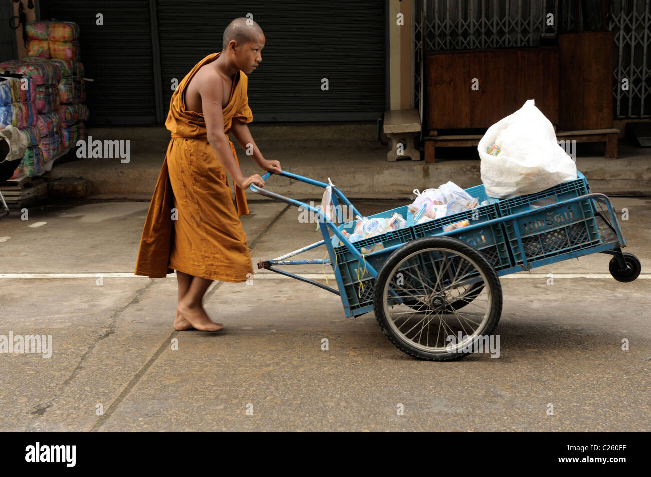 young novice monk pushing cart with food collecting on morning alms round , mae sot, northern thailand Stock Photo