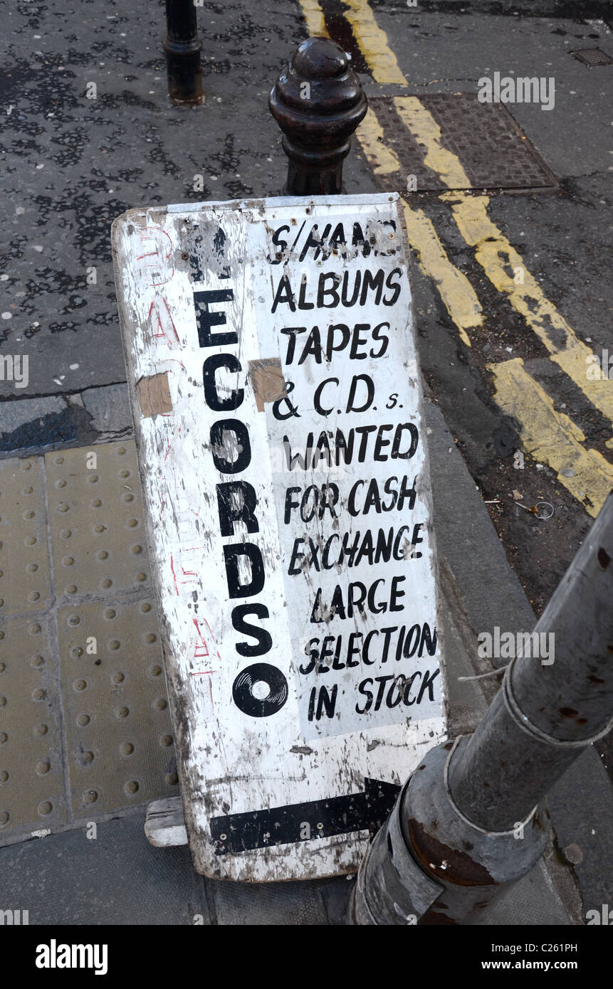 A weather beaten sign outside a secondhand record shop advertising its wares. - Stock Image