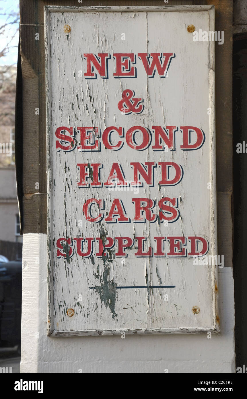 Weather beaten sign advertising new and used cars - Stock Image