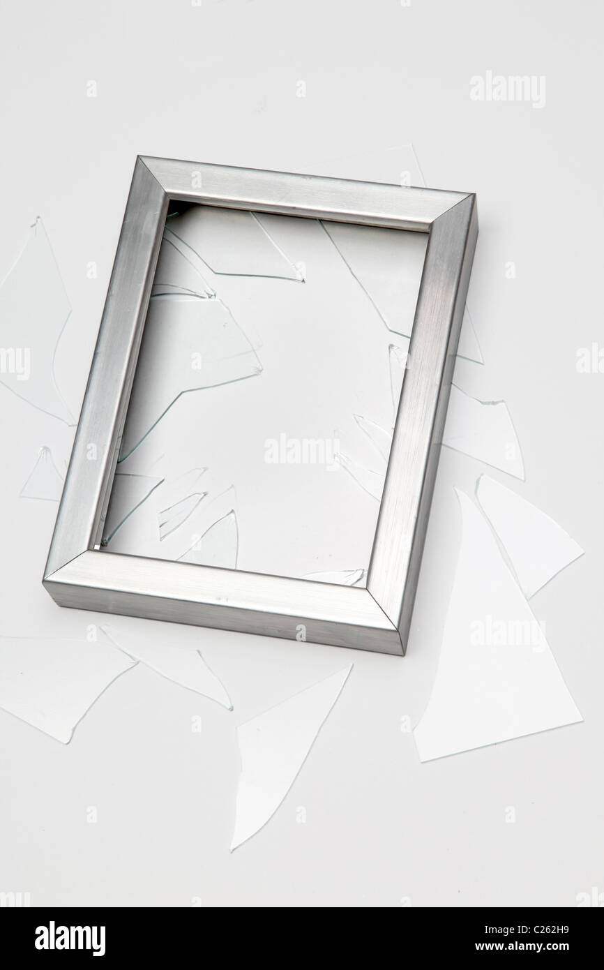 Empty silver coloured picture frame, broken with shattered glass - Stock Image