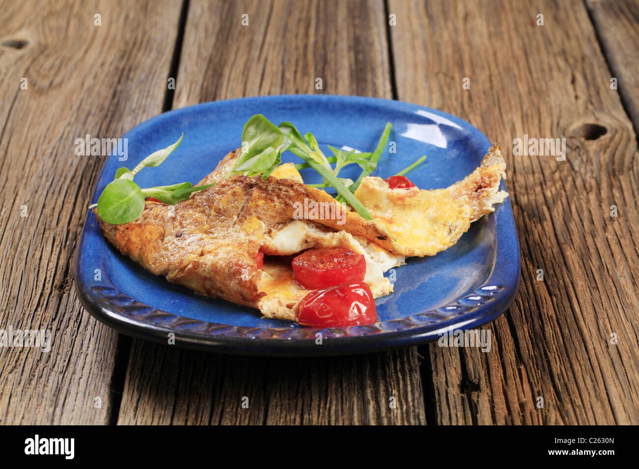 Egg omelet with tomatoes and salad greens - Stock Image