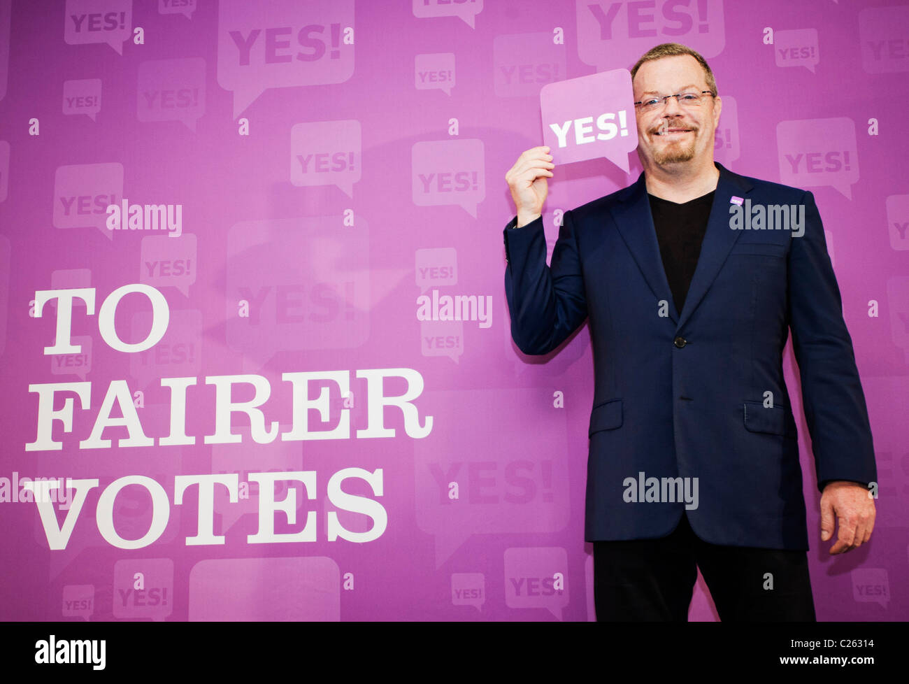 Eddie Izzard holds up a YES! card as he shows his support for the YES! to Fairer Votes campaign launched in London. - Stock Image