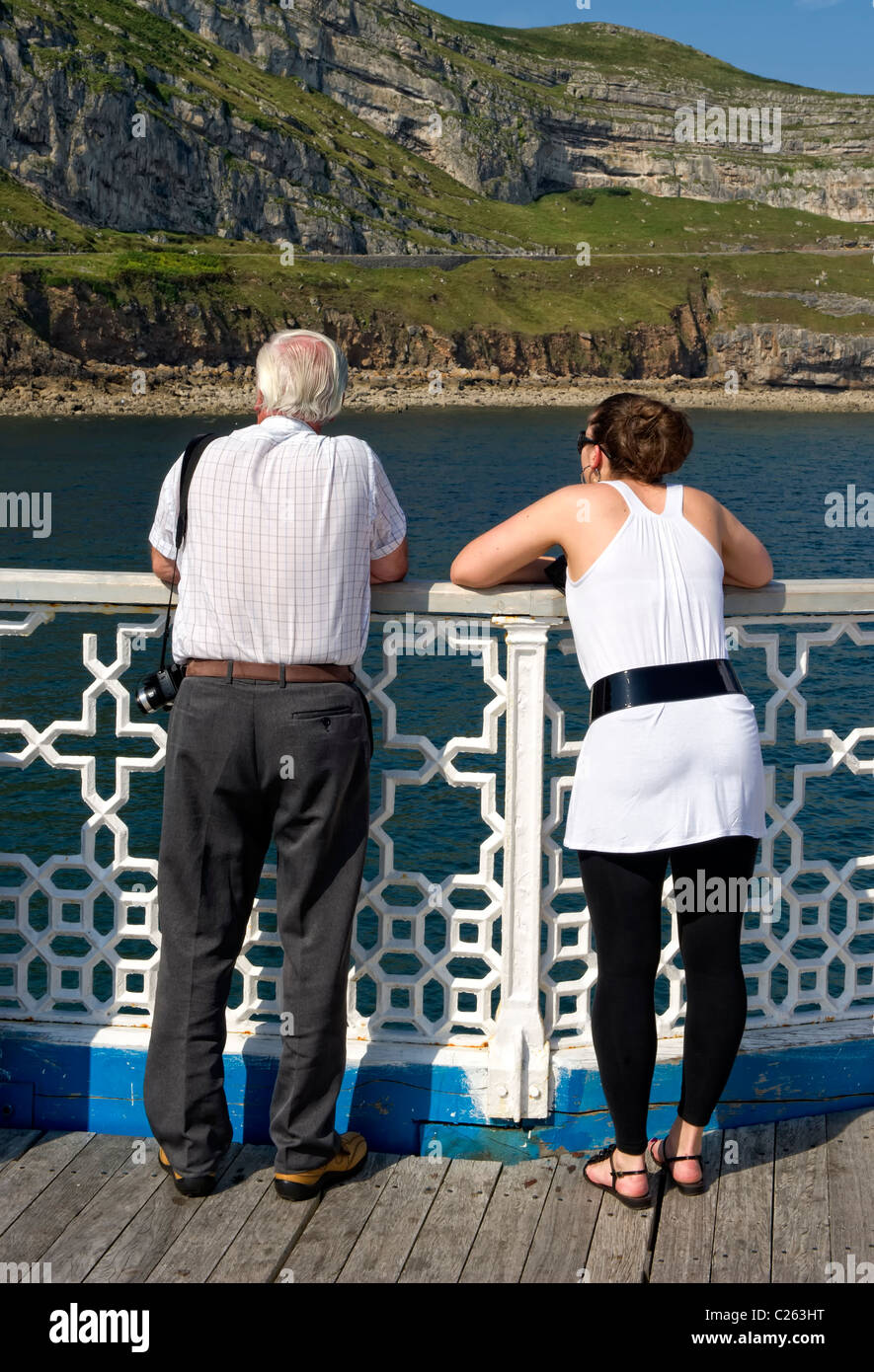 Man and woman leaning on the rail of Llandudno Pier and looking toward the Great Orme - Stock Image