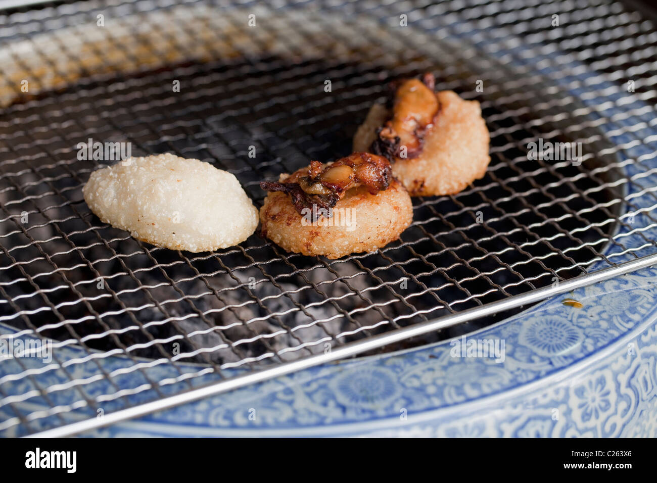 Rice balls topped with seafood grilling over charcoal in ceramic container, Miyajima, Japan - Stock Image