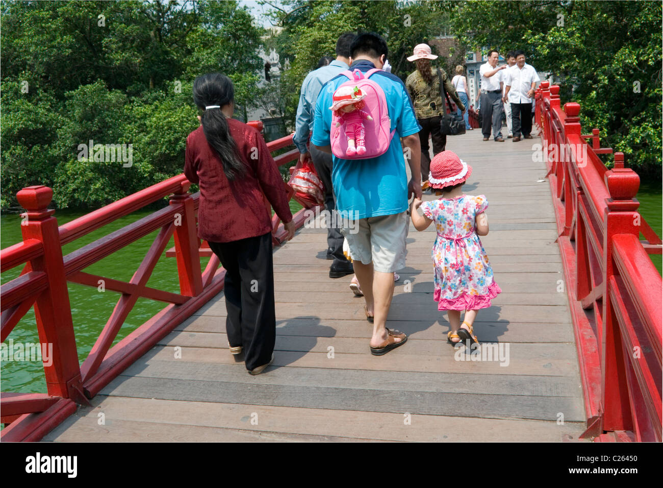 Family crossing the bridge to Quan Thanh Temple on Truc Bach Lake in Hanoi, Vietnam. - Stock Image