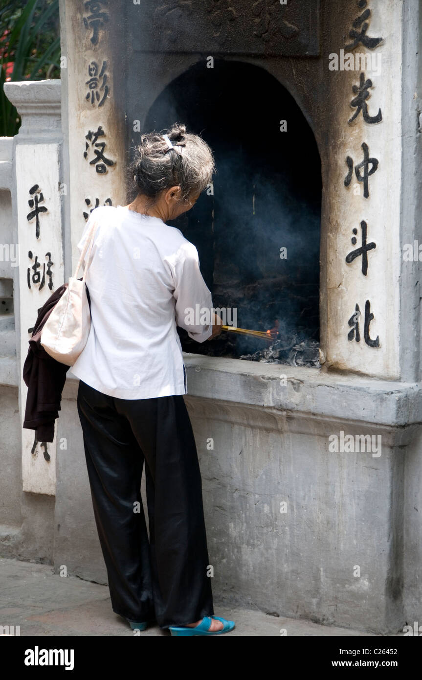 Woman lighting incense at Quan Thanh Temple on Truc Bach Lake in Hanoi, Vietnam. - Stock Image