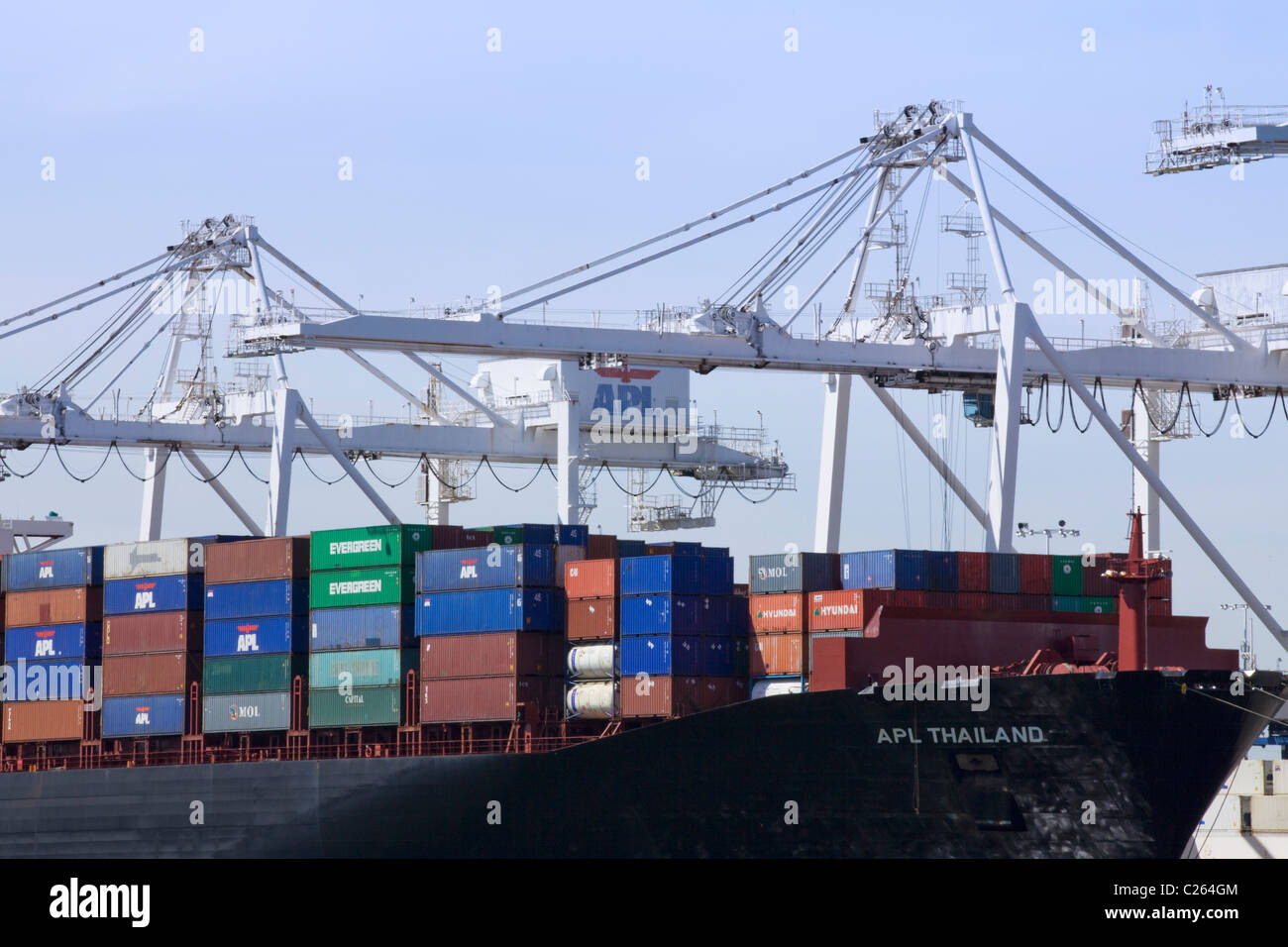 Loading shipping containers on ship - Stock Image