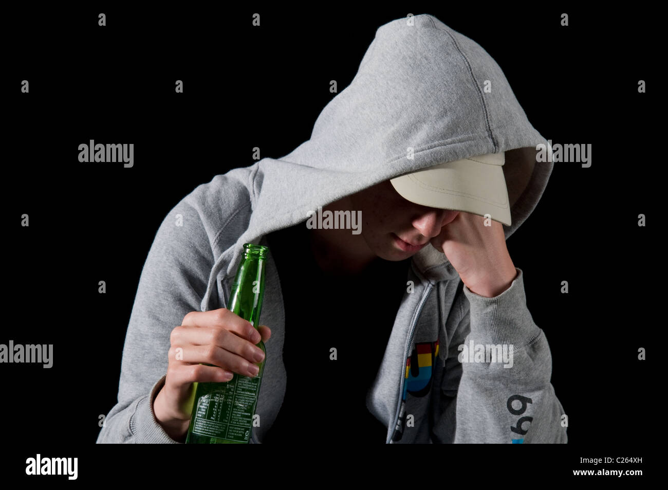 Depressed teenaged boy in hoody smoking and drinking