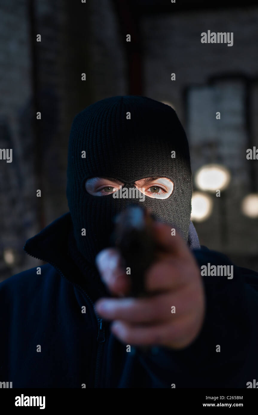 Man/terrorist wearing a black balaclava, pointing a handgun at the viewer - Stock Image
