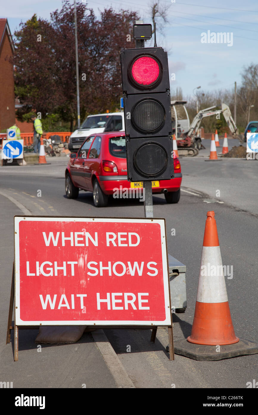 Red temporary traffic lights at road works. - Stock Image