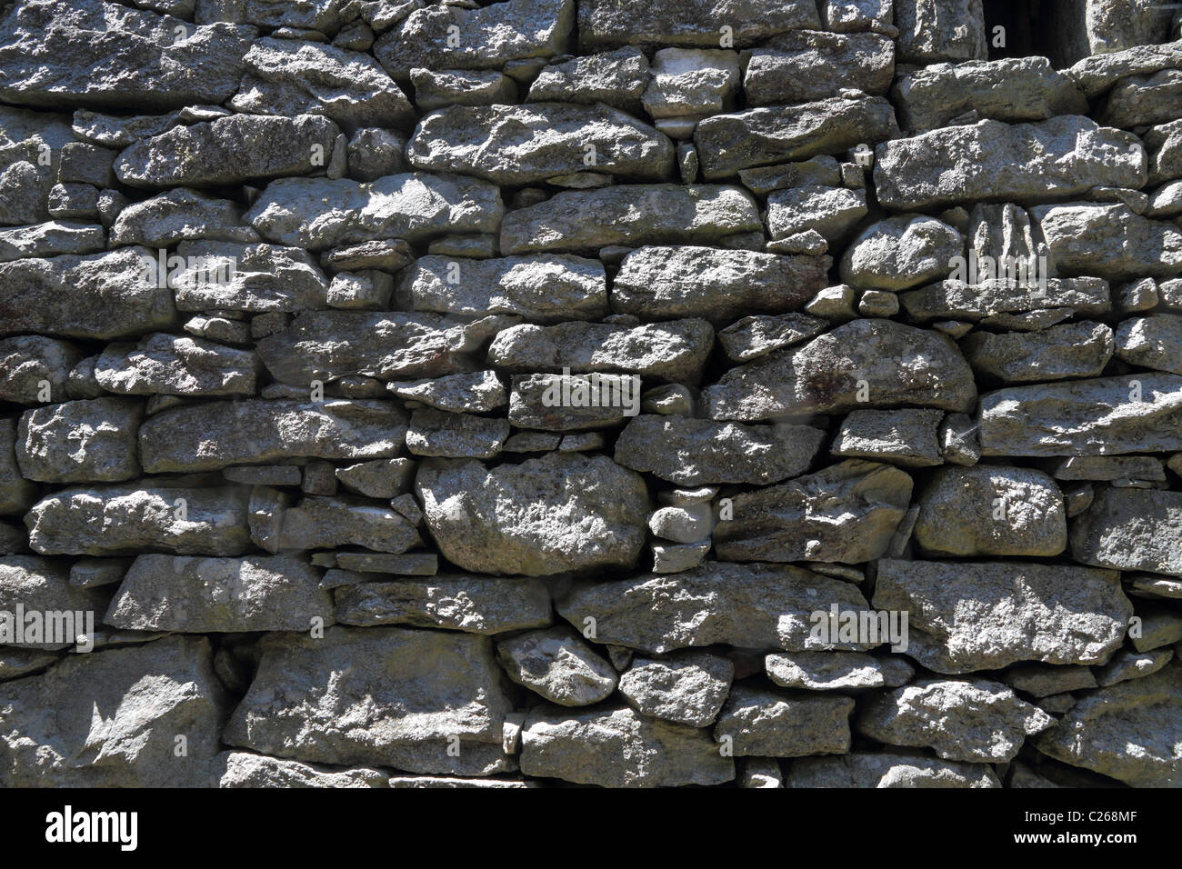 drystone wall put up put of gray rock slanted by the sun - Stock Image