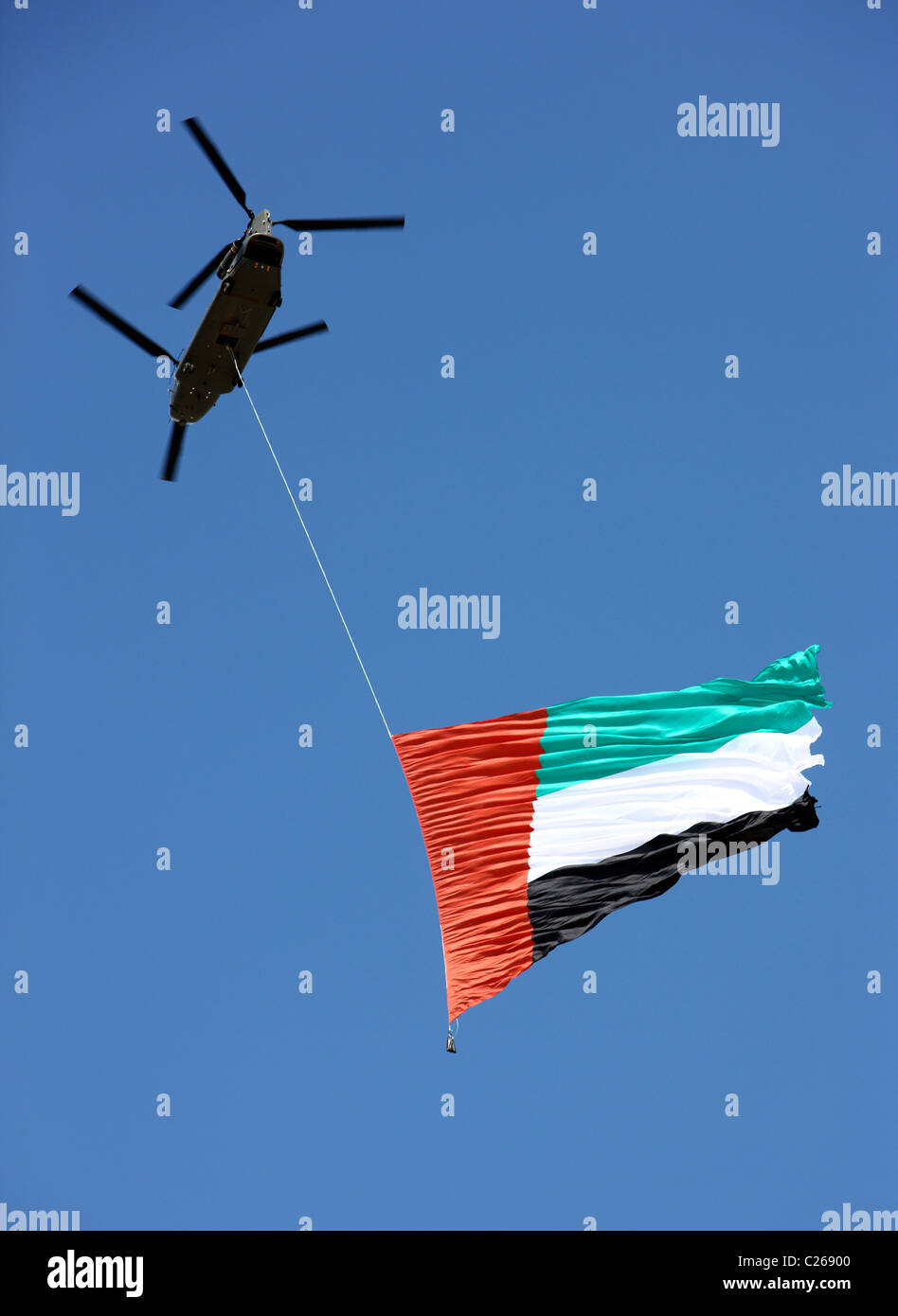 Military helicopter carries the national flag of the United Arab Emirates over the capital  Abu Dhabi. During a Stock Photo