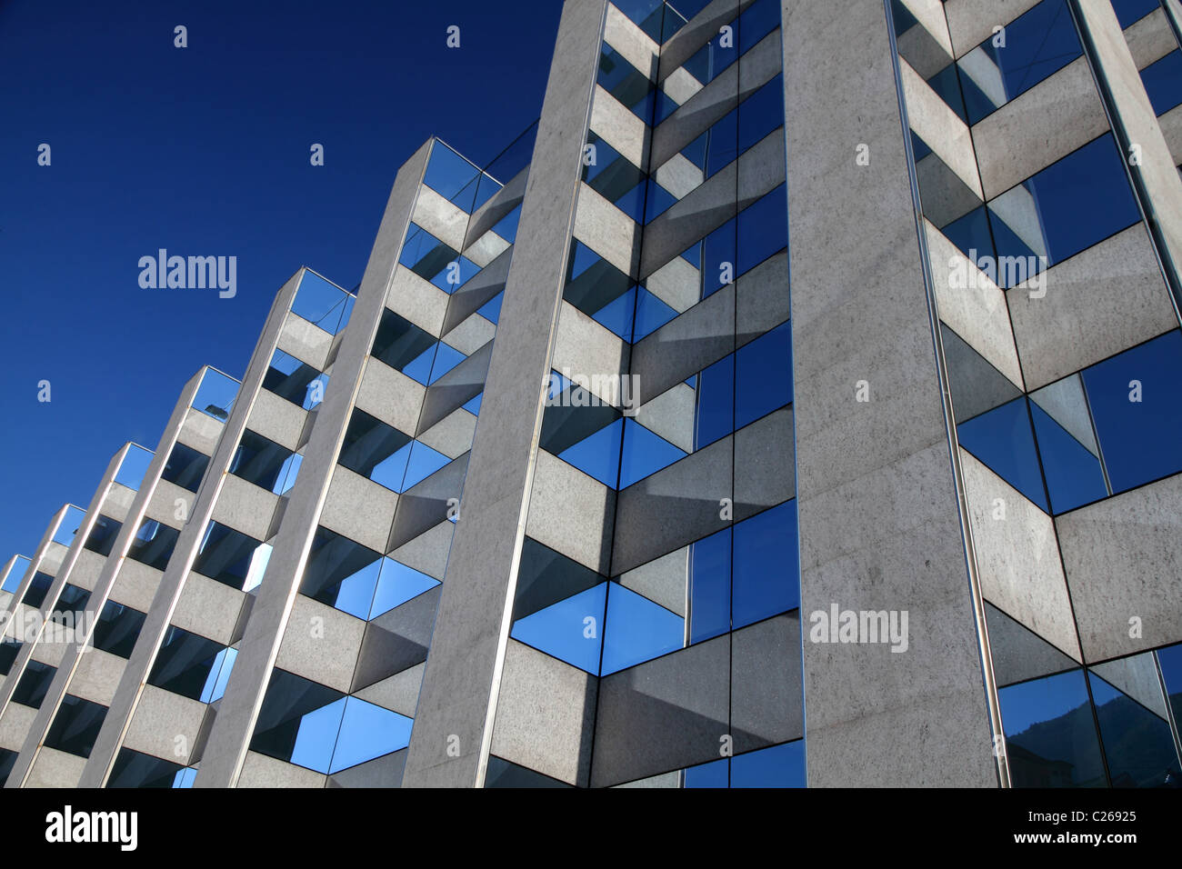 modern symmetrical office building facade with reflecting windows in front of a blue sky - Stock Image
