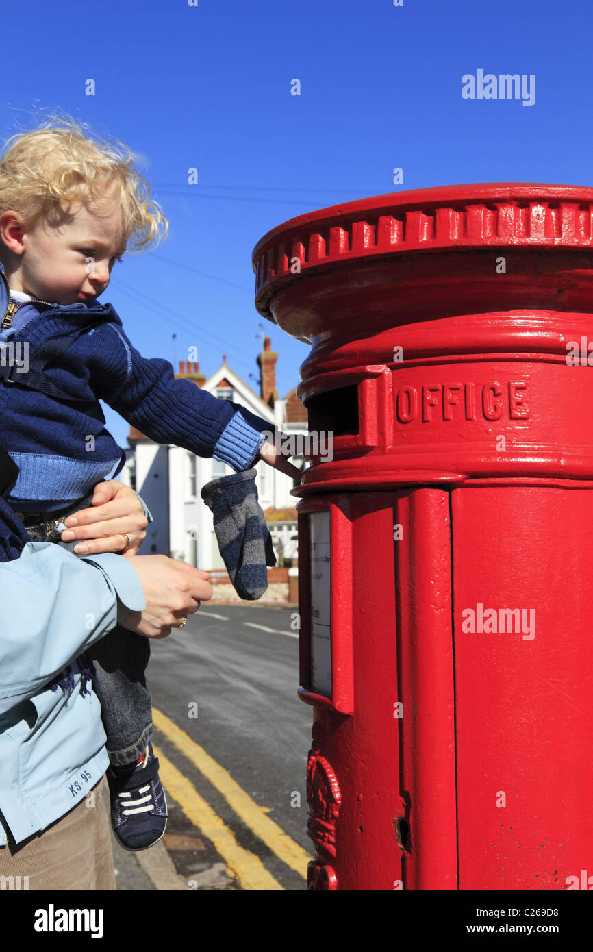 A toddler posting a letter. - Stock Image