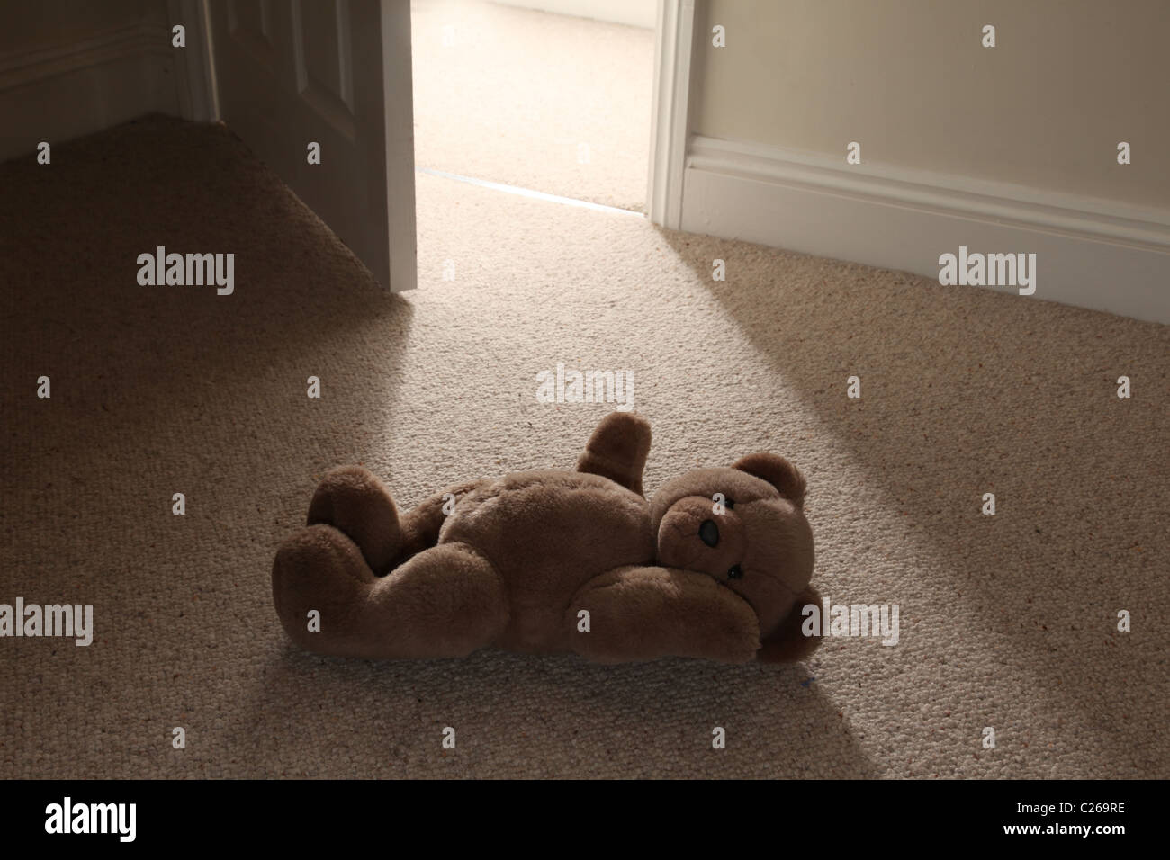 A teddy on the floor by an open door. - Stock Image