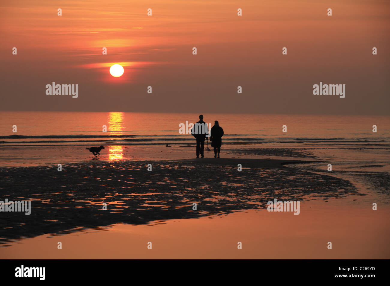 A couple watch the sunset over the sea at Birling Gap, East Sussex, England. - Stock Image