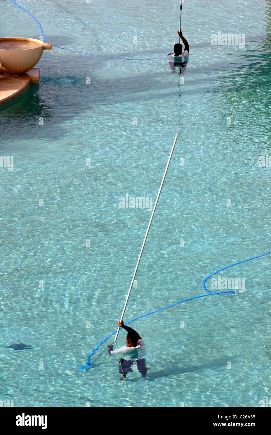 A swimming pool is cleaned by hotel staff with special underwater vacuum cleaners. - Stock Image
