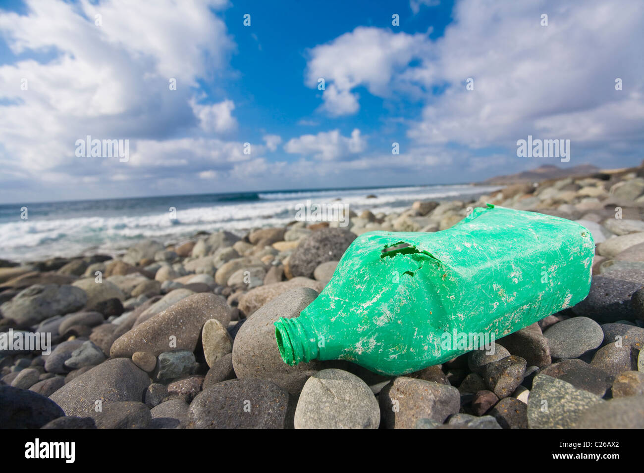 An old oil bottle lying on a rocky shore. Nice shot for biodegradable or environment concepts. - Stock Image