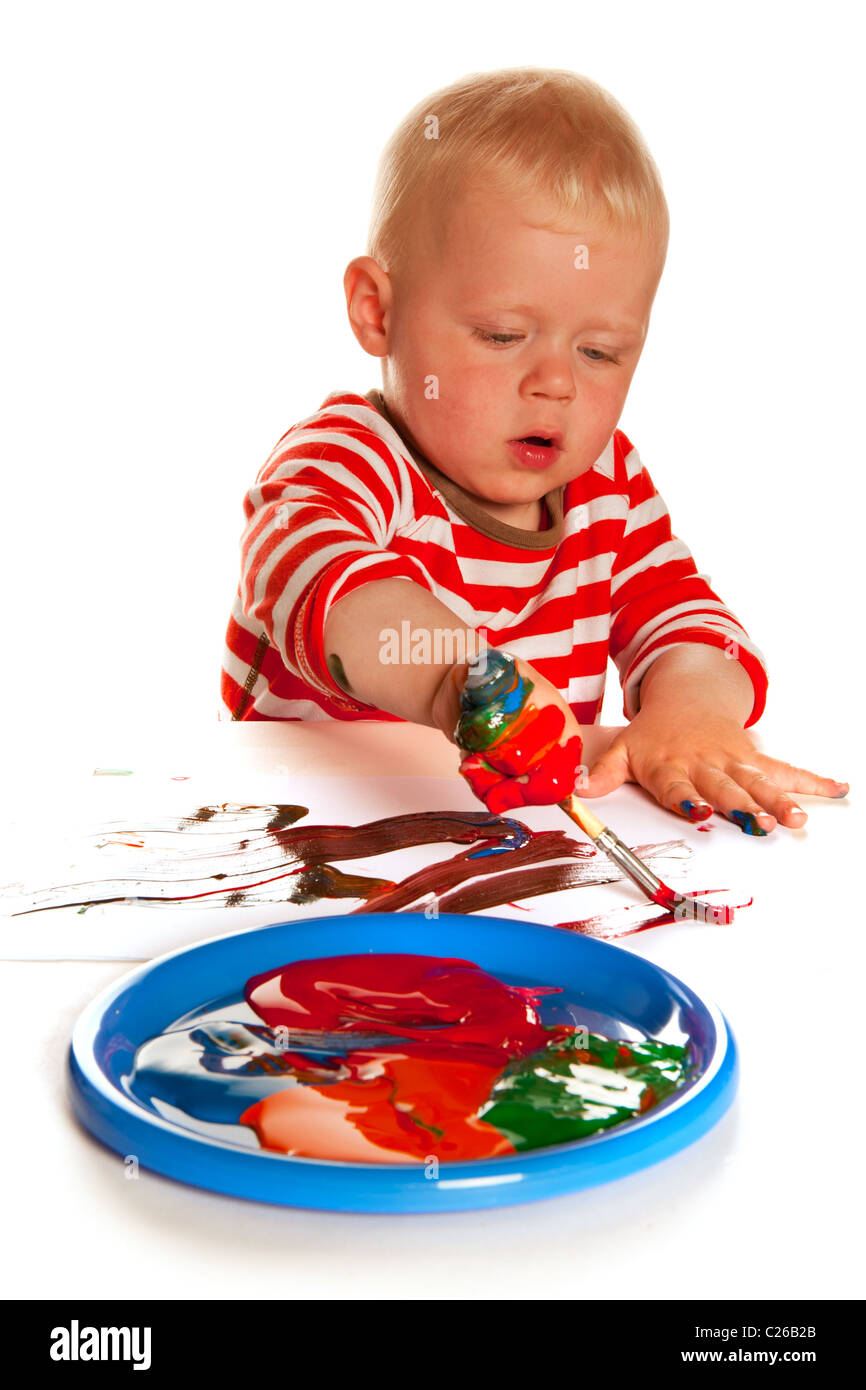 Little boy is painting and making a mess - Stock Image