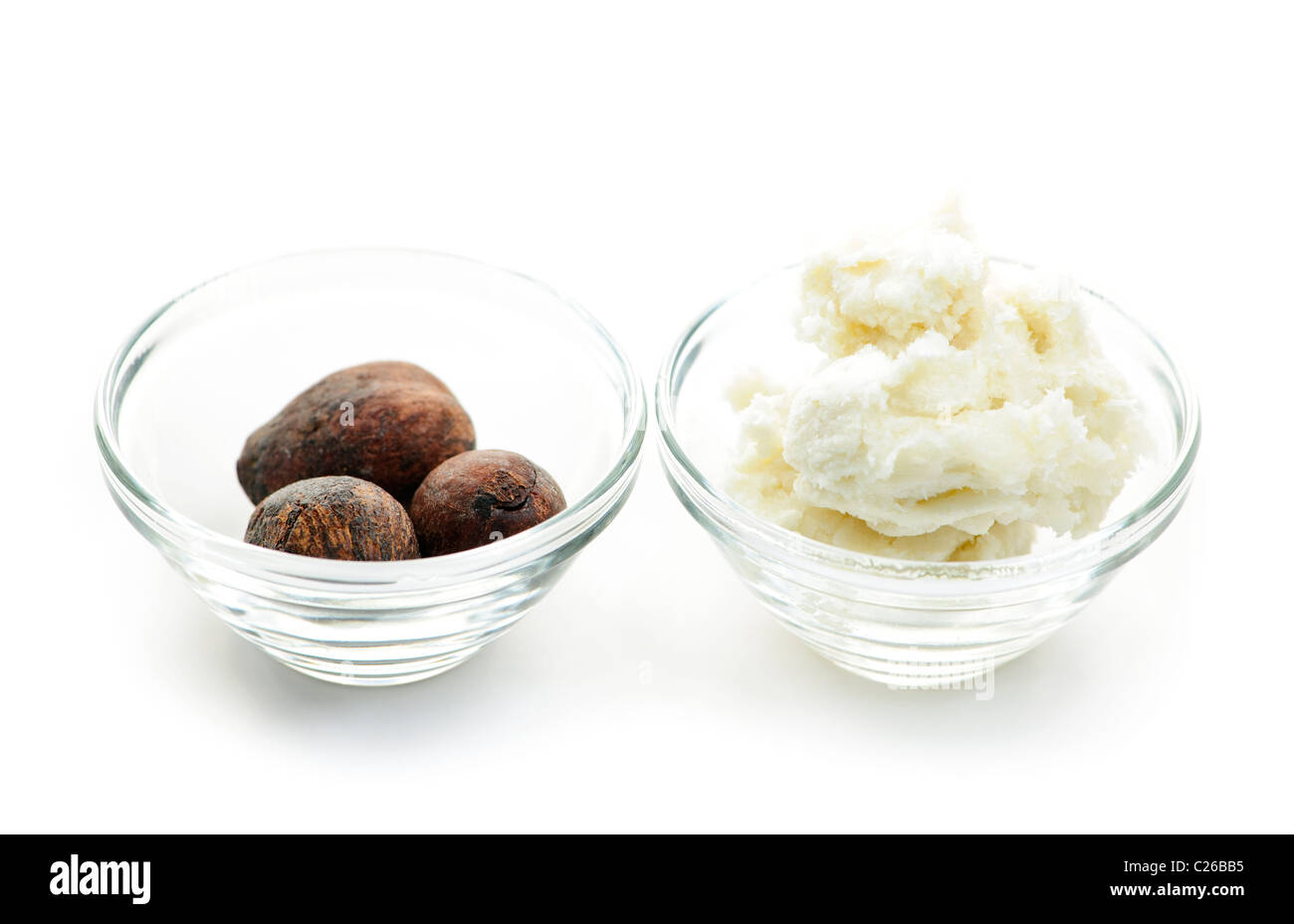 Shea butter and nuts in glass bowls isolated on white Stock Photo