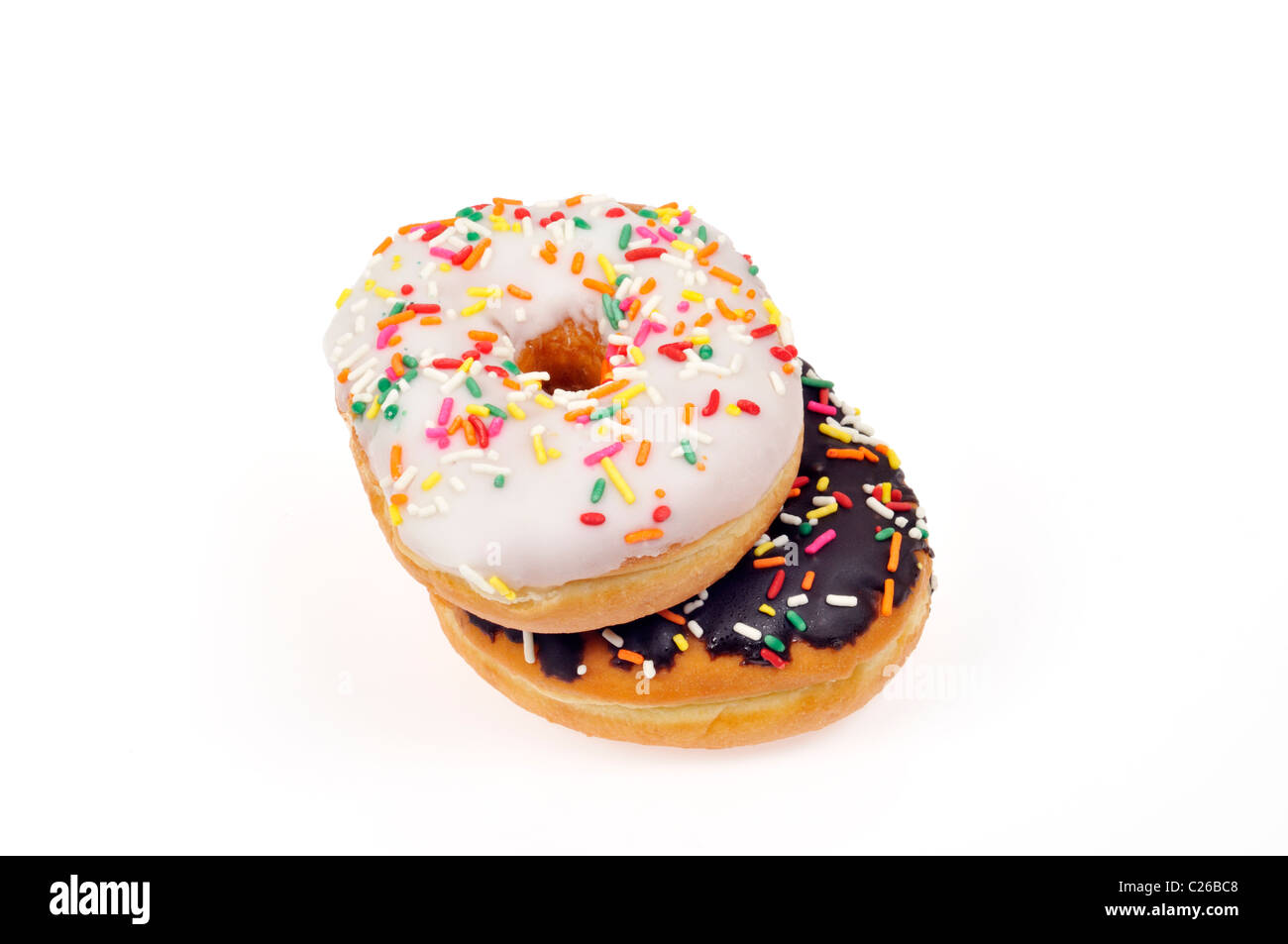 Vanilla frosted doughnut and chocolate frosted donut with colorful sprinkles on white background, cut out. - Stock Image